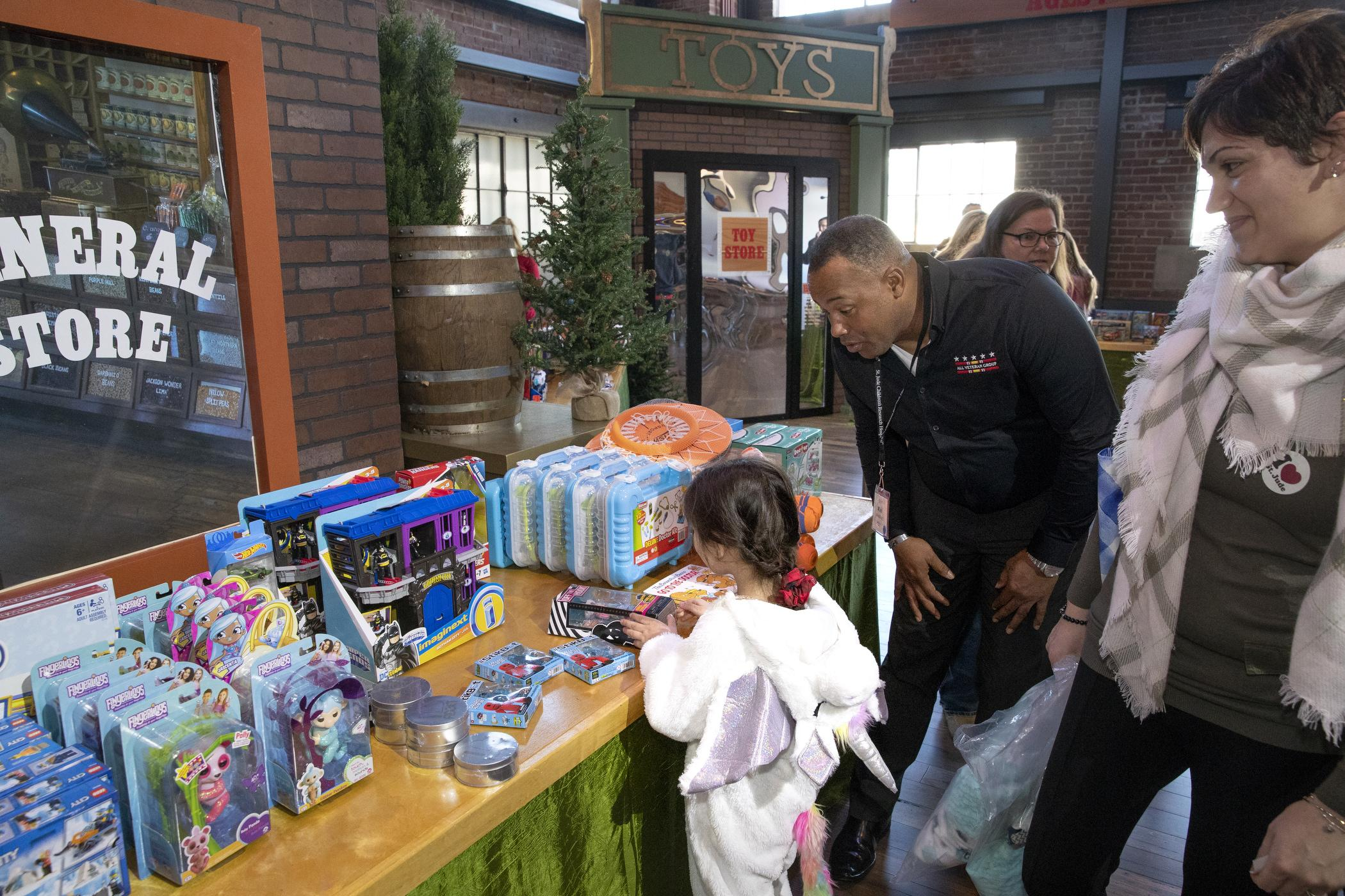 Child picks out gift from display table during Window World Day celebration at St. Jude