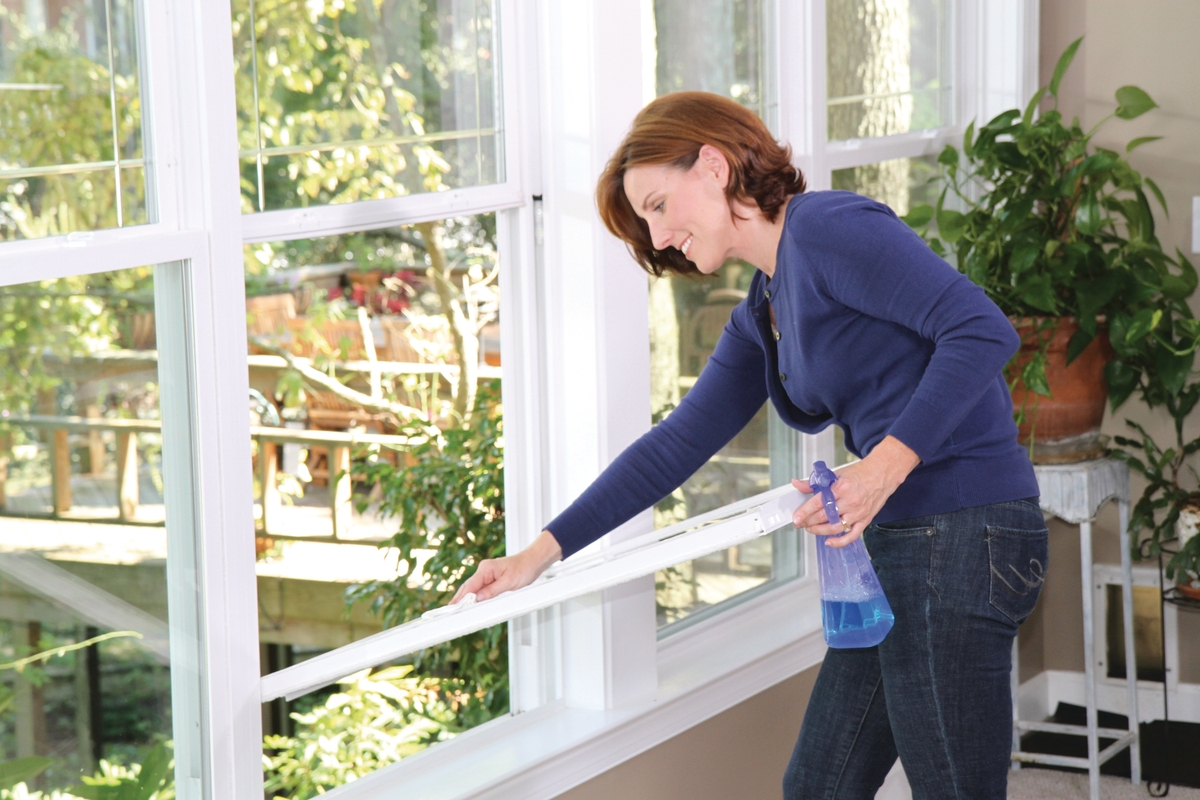 A woman cleaning a double-hung window