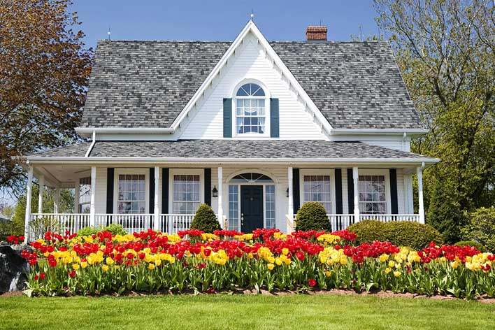White farmhouse-style home with colorful flowers in front