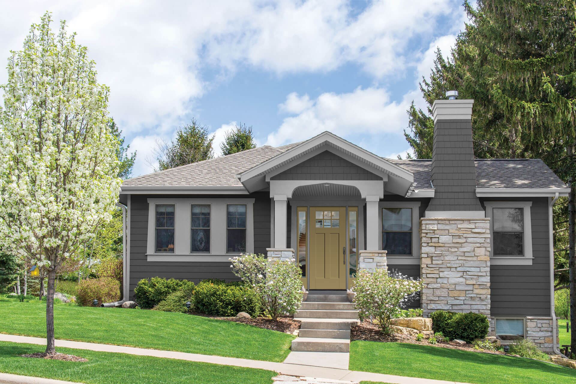 A gray house with bushes around the front door for landscaping