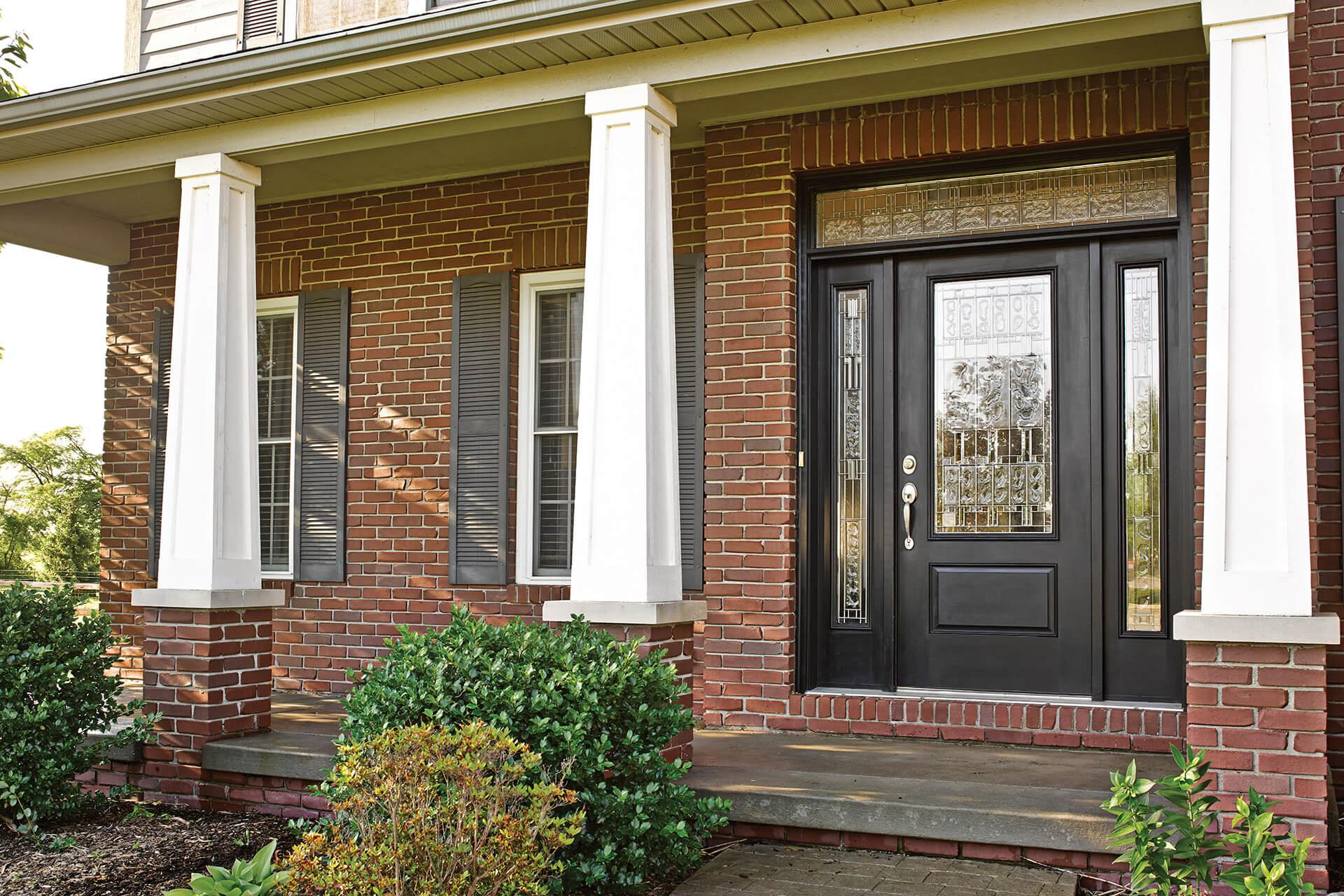 A brick home with columns and an exterior door features decorative glass