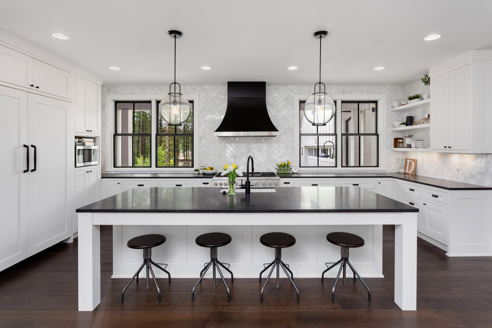 A beautiful kitchen in black and white with wooden flooring