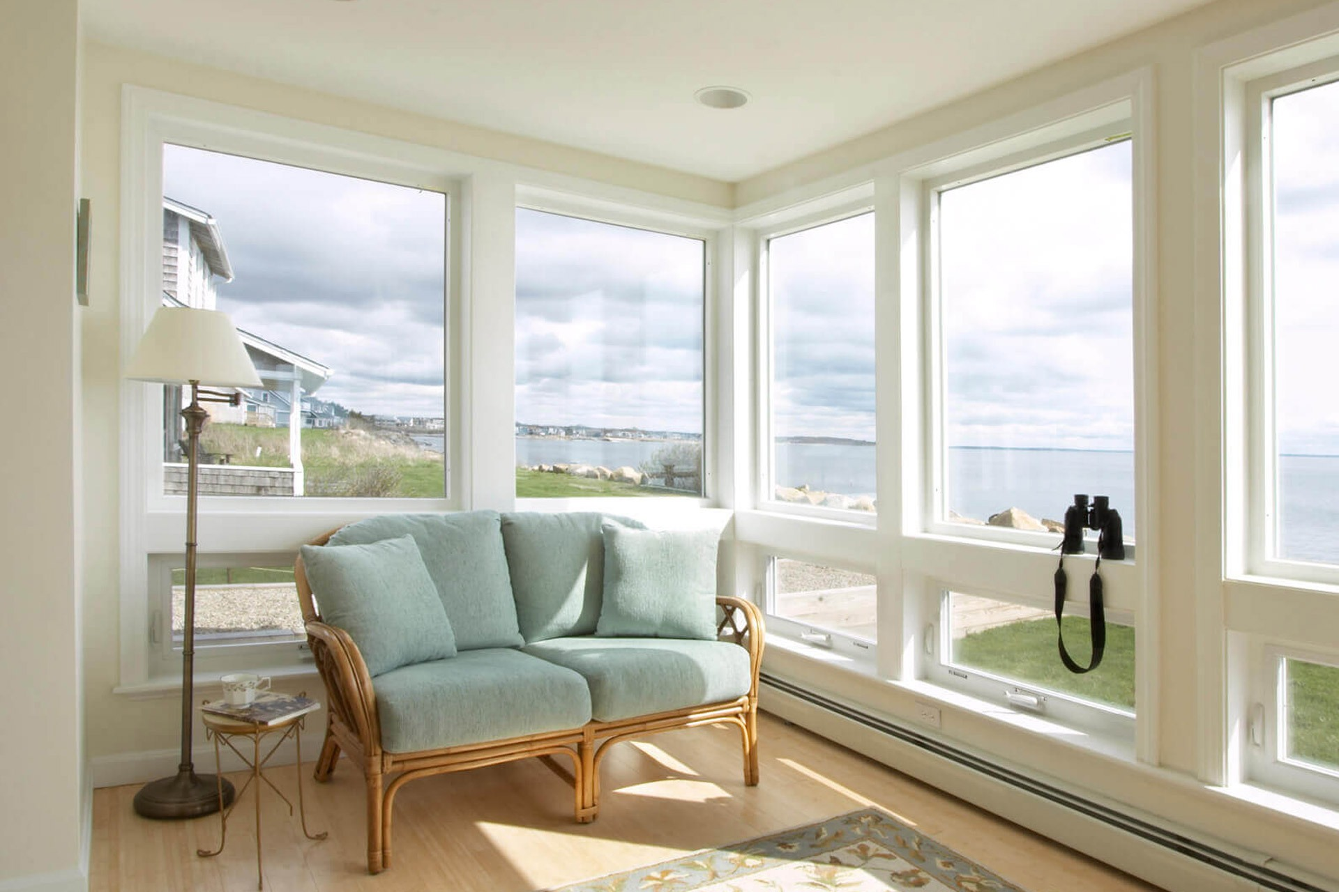 A sitting area in a beachfront home with floor-to-ceiling windows that a homeowner will need to prepare for hurricane season