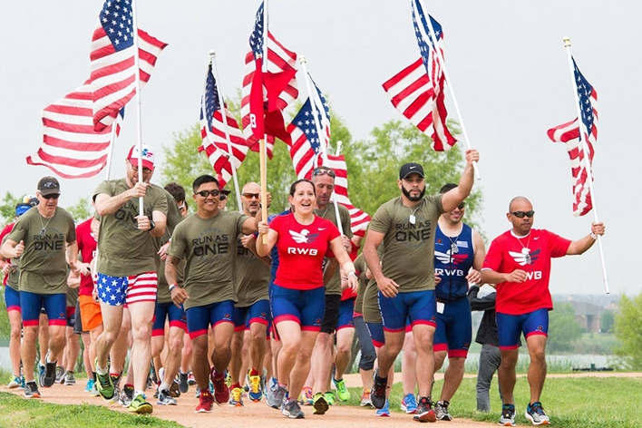 Smiling people carry the American flag for a good cause