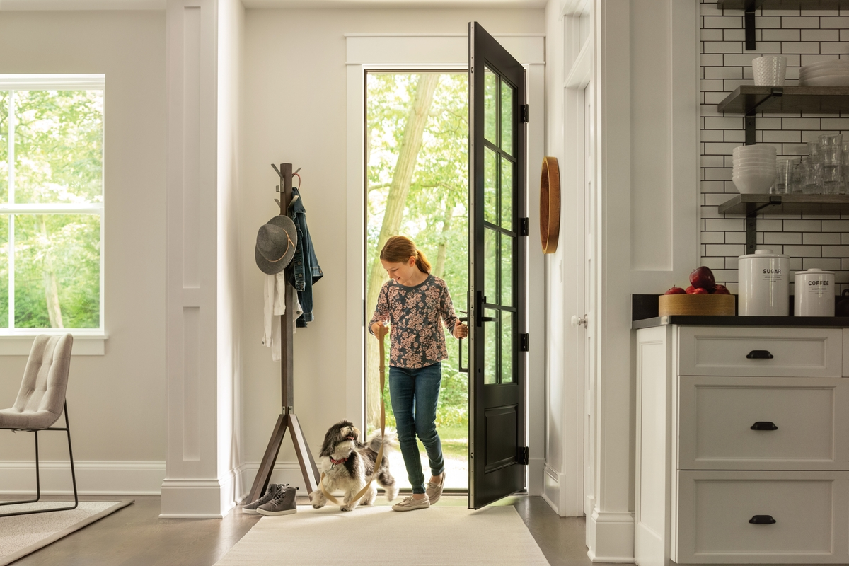 Girl entering front door of home with dog