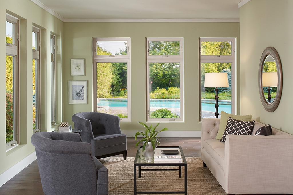 Sitting room with multiple windows facing a swimming pool outside during hot weather