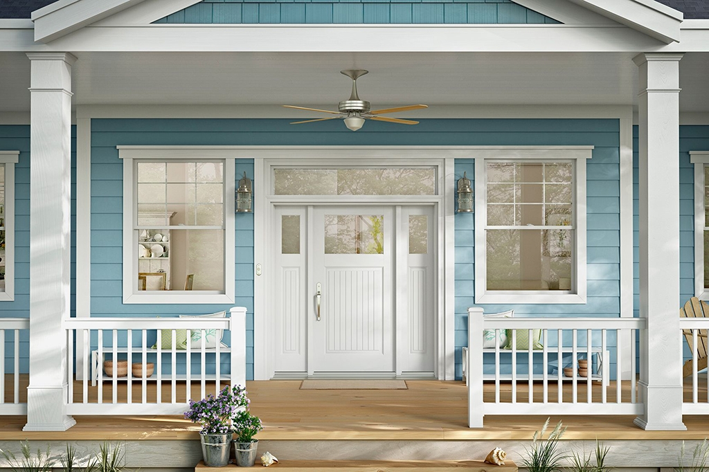 Front porch of a house in summer with blue siding and white windows and door