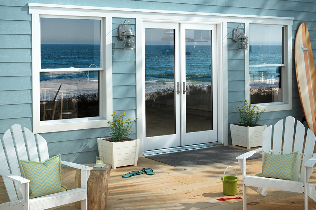Back porch or patio of home with blue siding and white trim on doors and windows