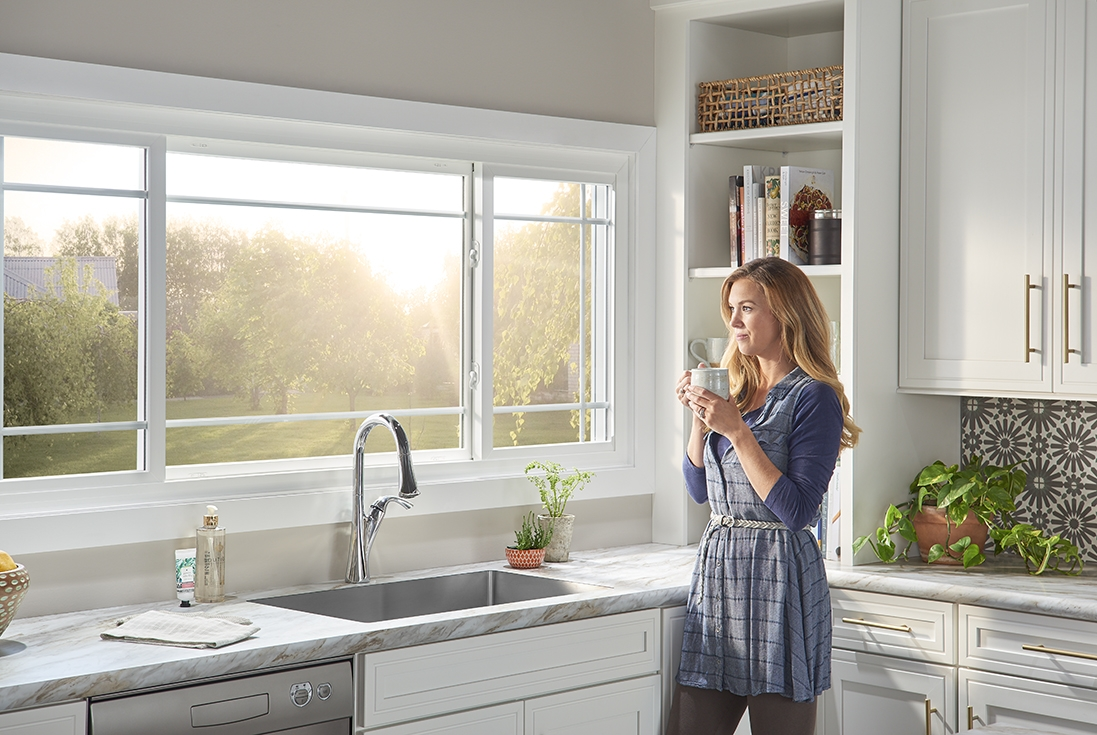 Woman enjoys morning sun from her kitchen window