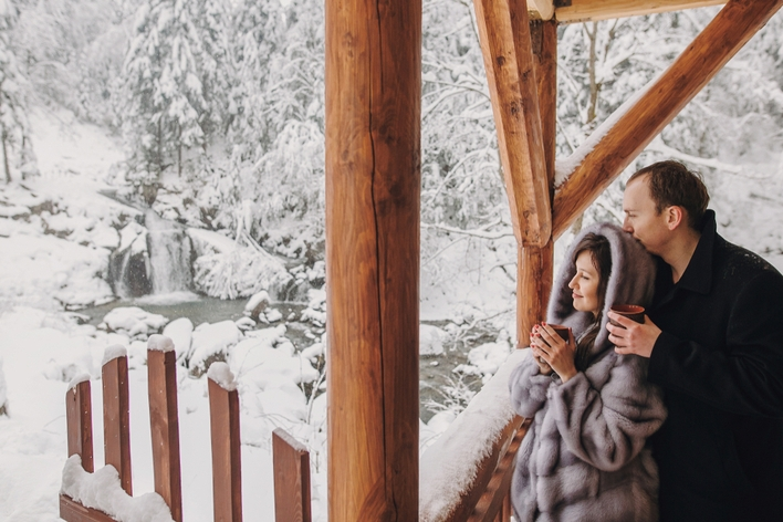 Couple watches snow together from porch