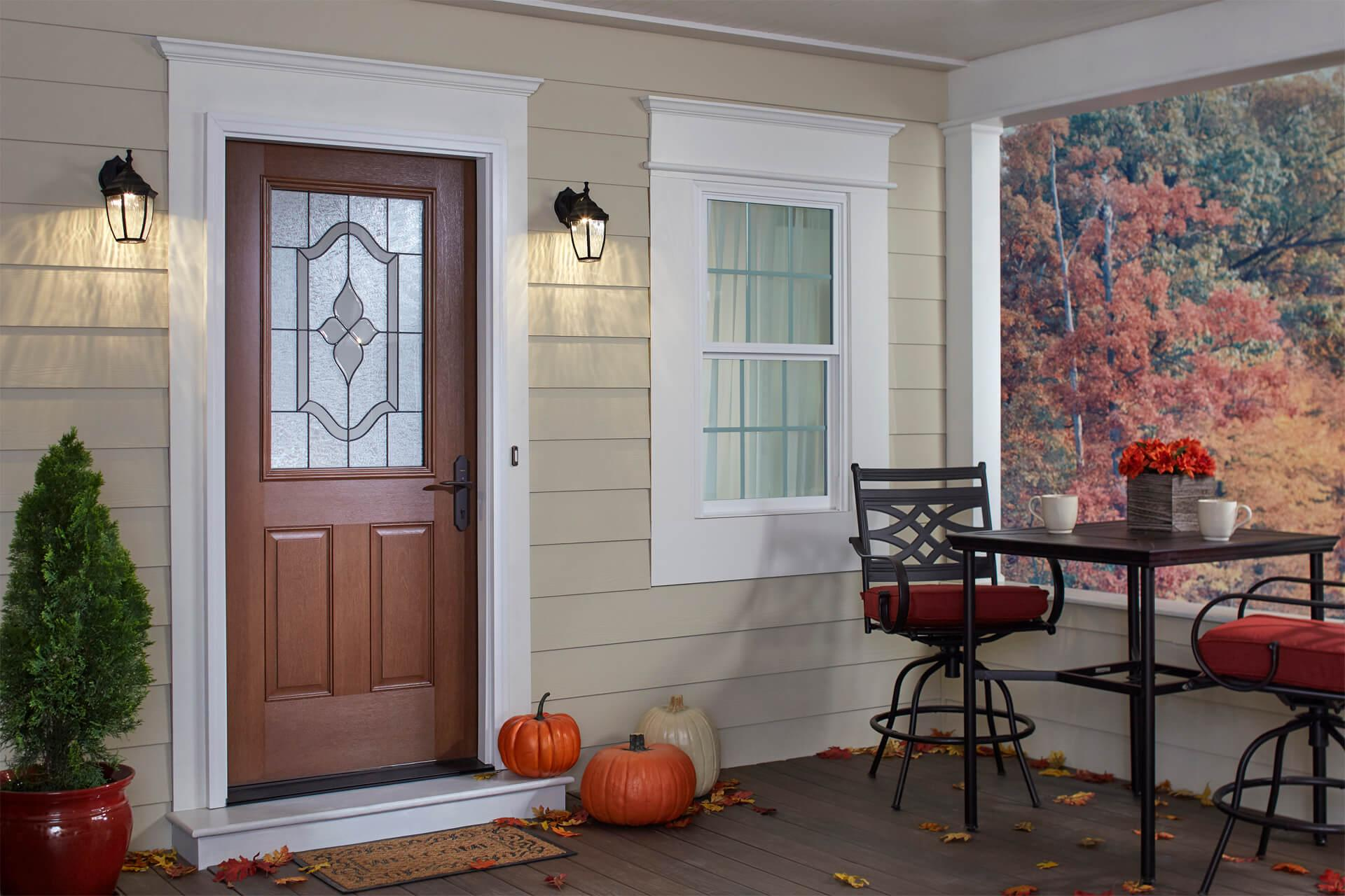 A front door with fall pumpkins sitting on the porch