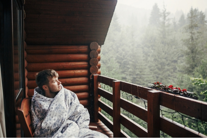 Man snuggled in blanket on porch watching the rain
