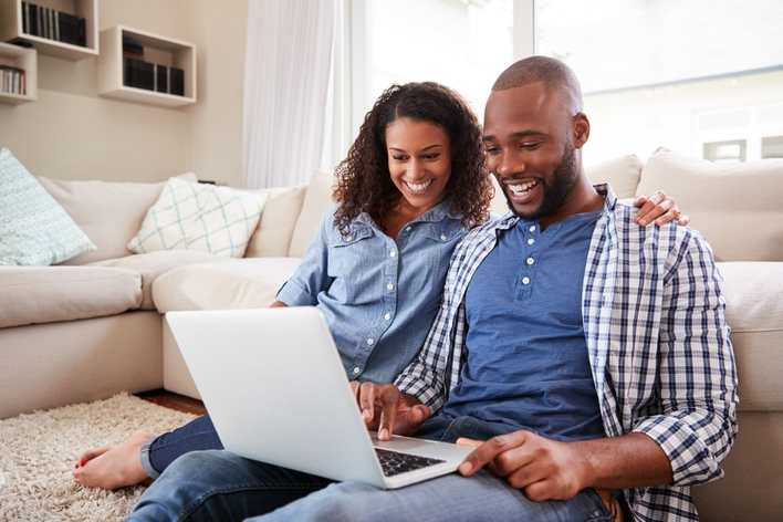 happy couple looking at laptop in living room