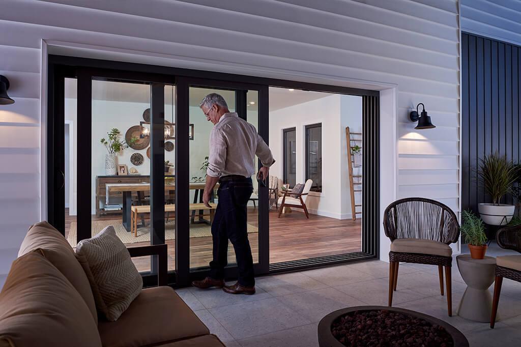 Man closing multi-panel sliding patio door