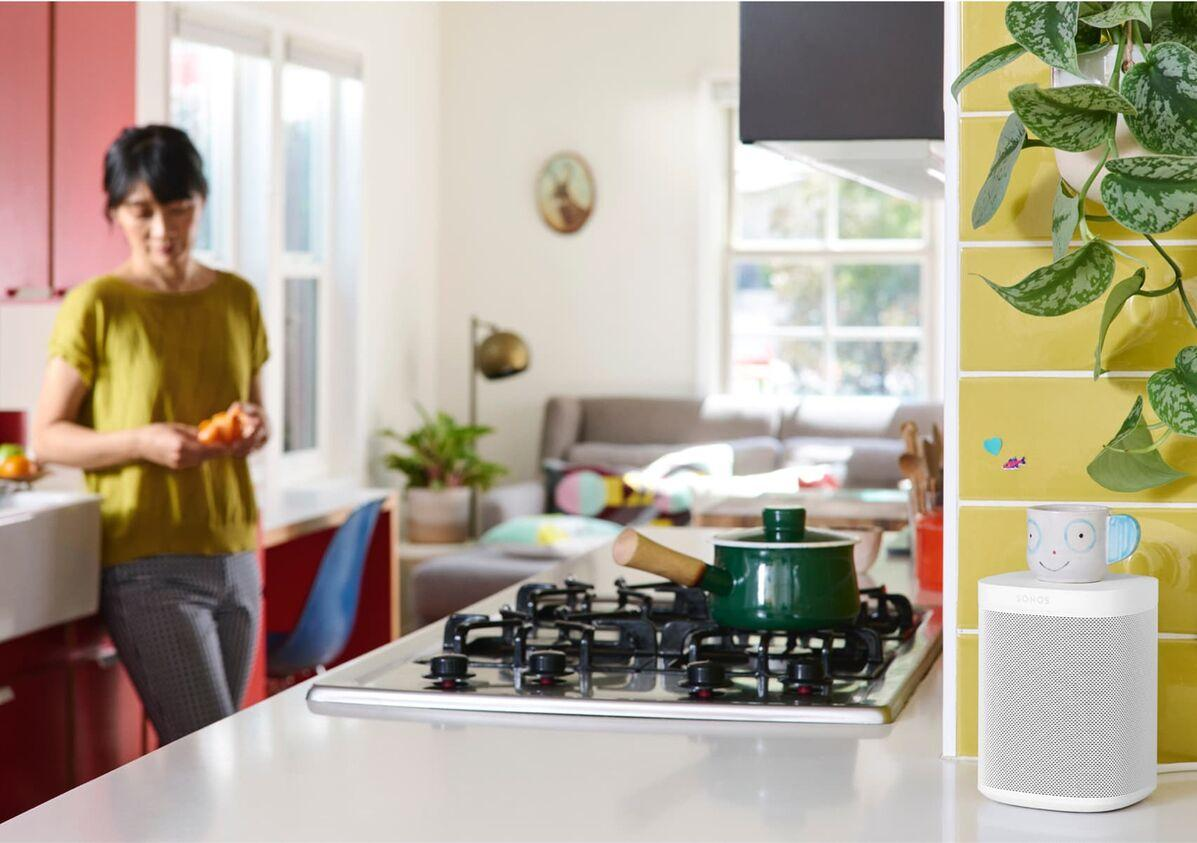 Woman in kitchen with smart speaker in foreground