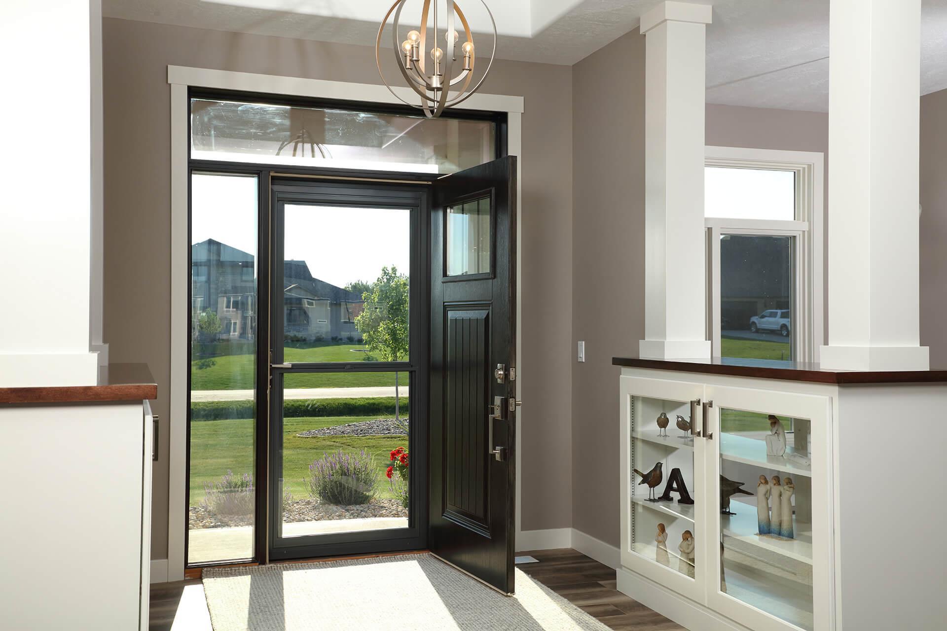 An entryway with an open entry door letting sunlight in through the storm door