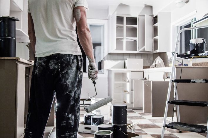 Man painting his kitchen cabinets