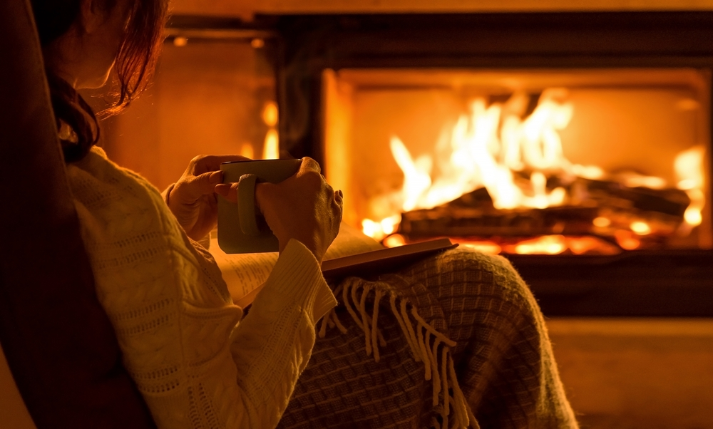 Woman sitting by fire with coffee