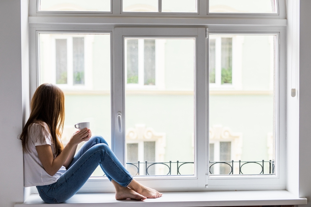 Woman sitting by window with coffee