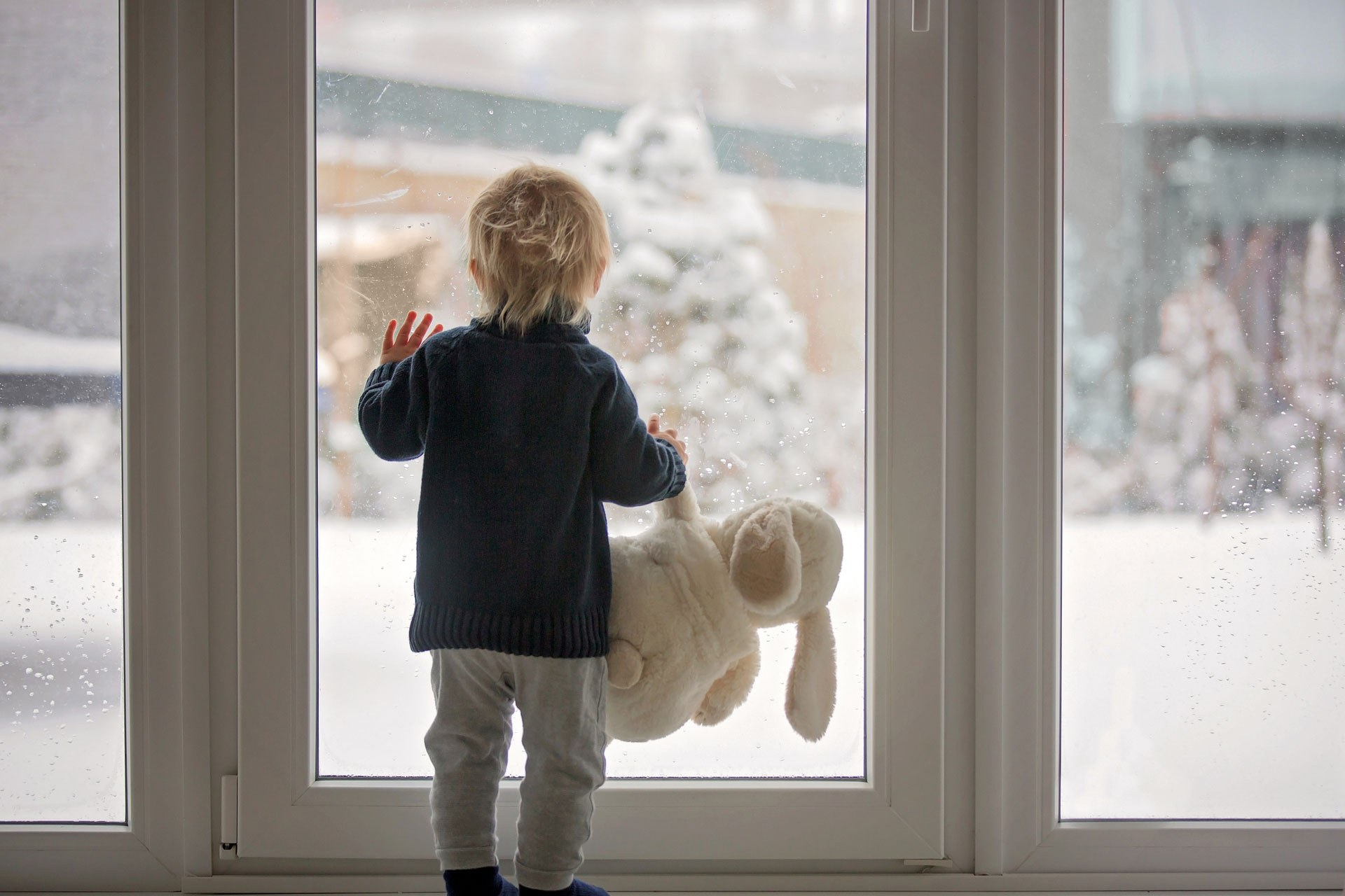 Young Boy Looking Out Window In Winter Too